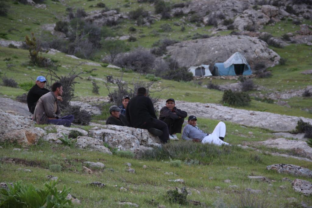 Рабочие на отдыхе на фоне своей палатки